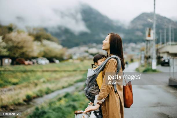 Young Asian mother carrying cute little toddler girl walking outdoors and taking a deep breath against the beautiful nature scene