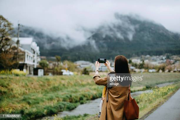 young asian mother carrying little toddler girl walking outdoors and photographing the beautiful nature scenics with smartphone while on vacation - capturing an image stock pictures, royalty-free photos & images