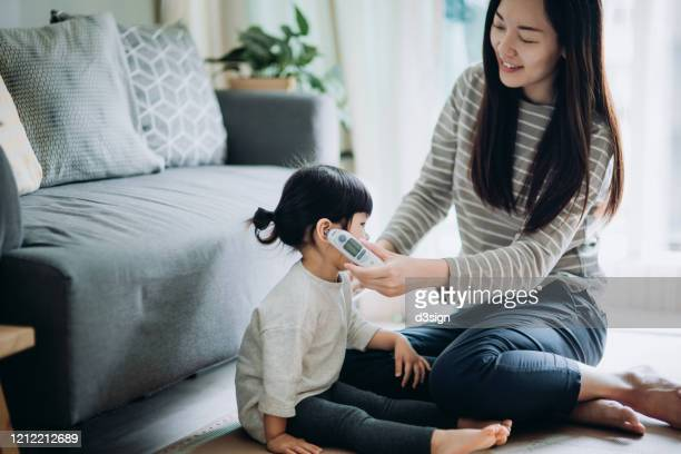 young asian mother checking daughter's temperature with a digital thermometer in the living room - digital thermometer ストックフォトと画像