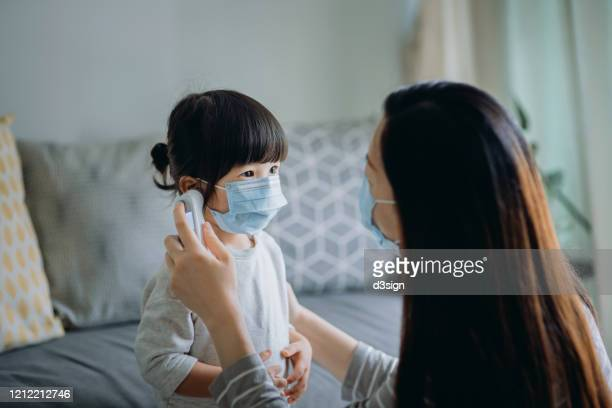 young asian mother checking sick daughter's temperature with a digital thermometer in the living room, both of them are wearing a surgical mask to prevent the spread of cold and flu and viruses - image stock pictures, royalty-free photos & images