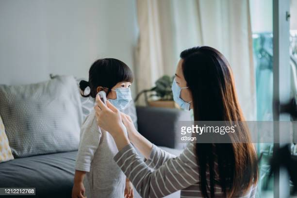 young asian mother checking sick daughter's temperature with a digital thermometer in the living room, both of them are wearing a surgical mask to prevent the spread of cold and flu and viruses - digital thermometer ストックフォトと画像