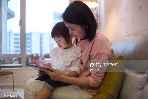 young asian mother educating daughter using latest technology from digital tablet - korean ethnicity stock pictures, royalty-free photos & images
