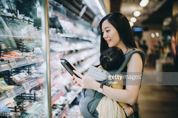 young asian mother grocery shopping with little daughter and choosing for fresh fish in the supermarket - 専業主婦 ストックフォトと画像
