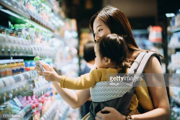 young asian mother grocery shopping with little daughter and choosing for organic baby food in the supermarket - リスト ストックフォトと画像