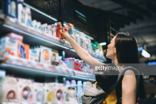 young asian mother grocery shopping with little daughter and choosing for baby necessities in a store - cleaning agent stock pictures, royalty-free photos & images