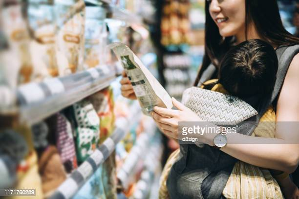 young asian mother grocery shopping with little daughter and choosing for organic baby food in the supermarket - 包装 ストックフォトと画像