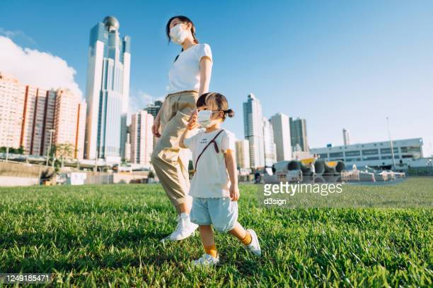 young asian mother holding hands with cute little daughter strolling in urban park in the city enjoying the warmth of sun and fresh air on a lovey sunny day, both are wearing a protective face mask - bronzage masque photos et images de collection