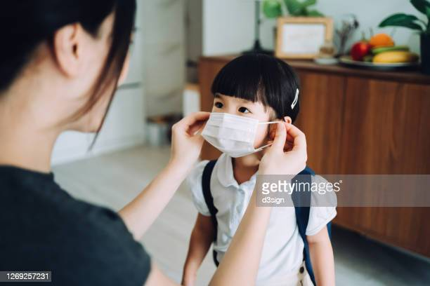young asian mother preparing for her little daughter's first day of school and putting on a protective face mask on her daughter's face to protect and prevent from the spread of viruses - first occurrence stock pictures, royalty-free photos & images