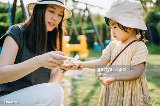 young asian mother squeezing hand sanitizer onto little daughter's hand in the outdoor playground to prevent the spread of viruses - 消毒薬 ストックフォトと画像