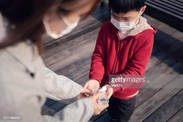 jonge aziatische moeder die handontsmettingsmiddel op de hand van weinig zoon perst om de verspreiding van coronavirus en covid 19 te verhinderen - hand sanitizer stockfoto's en -beelden