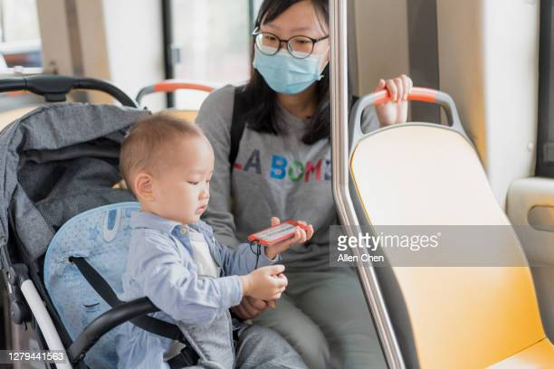 young asian mother takes her son on the bus - carriage stock pictures, royalty-free photos & images