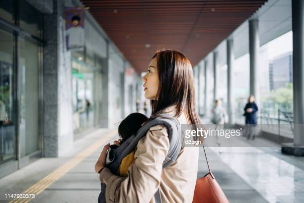 young asian mother taking care of little daughter while walking in downtown city street - 専業主婦 ストックフォトと画像