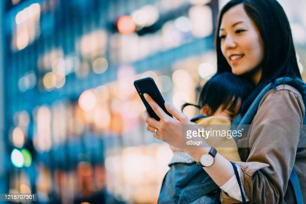 young asian mother using smartphone in downtown city street while shopping with little daughter - 仕事後 ストックフォトと画像