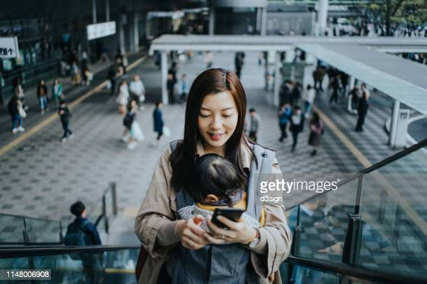 young asian mother with little daughter using smartphone while riding on escalator in downtown city, with busy commuters in the background - 駅 ストックフォトと画像