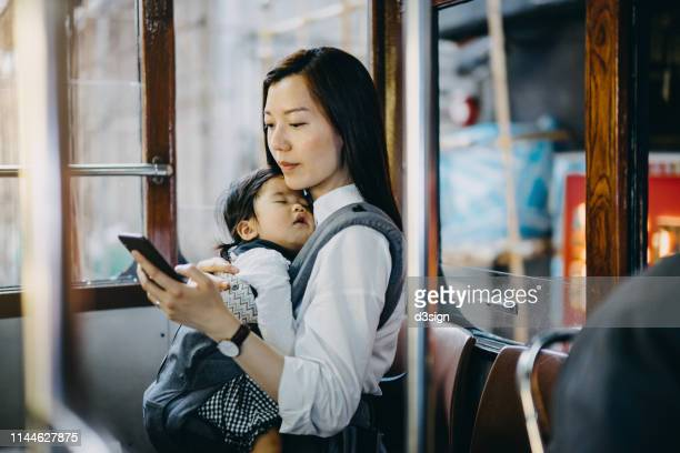 young asian mother with sleeping little daughter using smartphone while riding on tram in the city - 専業主婦 ストックフォトと画像
