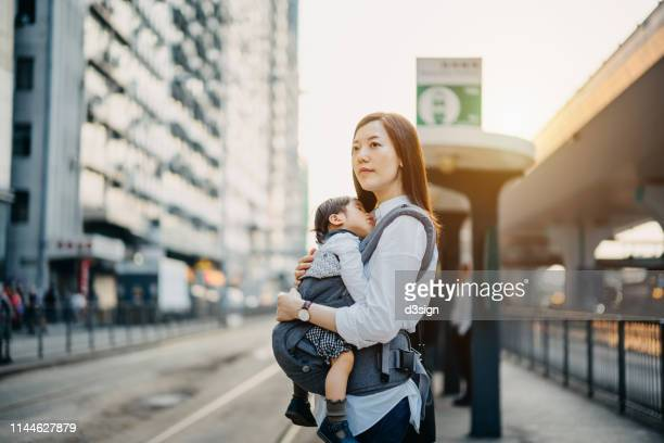 young asian mother with sleeping little daughter waiting for tram in the city - 専業主婦 ストックフォトと画像