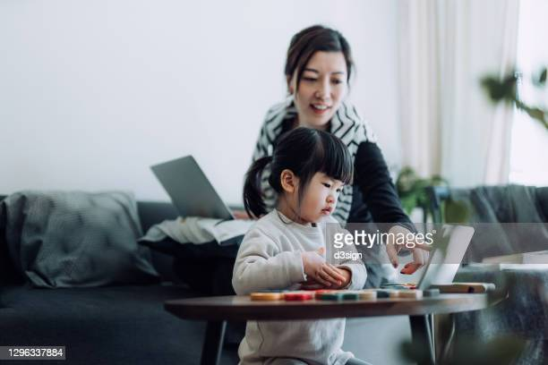 young asian mother working from home on laptop while homeschooling her daughter and assist her with school work. little daughter is studying from home and attending online school classes with a digital tablet. life in a quarantine - education stock pictures, royalty-free photos & images