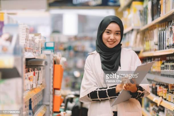 薬局店で働く若いアジアのイスラム教徒の薬剤師の女性 - 僧衣 ストックフォトと画像