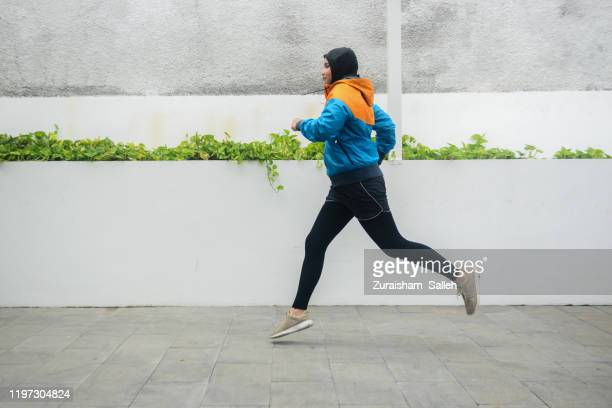 young asian muslim sportswoman in hijab running on jogging track - center athlete stock pictures, royalty-free photos & images