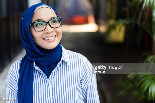 Young Asian Muslim Woman with smile on her face.