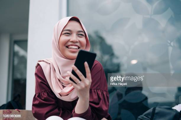 young asian muslim women playing smartphone - muslim stock pictures, royalty-free photos & images