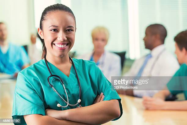 Young Asian nurse smiling during hospital staff meeting