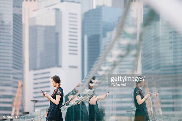 Young Asian office lady texting messaging in city