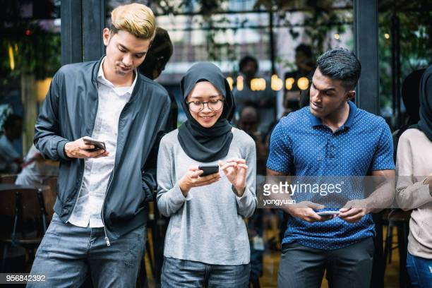 young asian people using smartphones - malaysia stock pictures, royalty-free photos & images