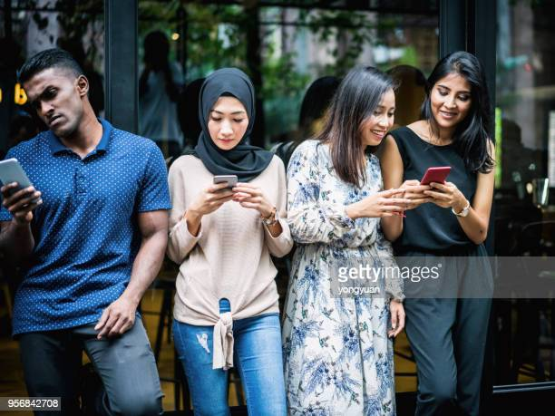 young asian people using smartphones - malay hijab stock photos and pictures