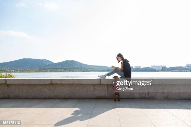 young asian pregnant woman reading at lakeside