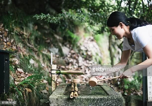 水に手を伸ばす若いアジア人 - 噴水 ストックフォトと画像