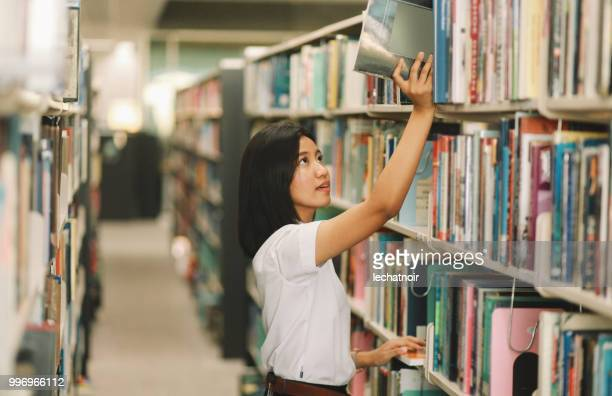 Junge asiatische Studentin sucht nach Bücher in der Bibliothek