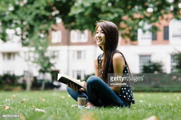 Young Asian Student Reading in Park London