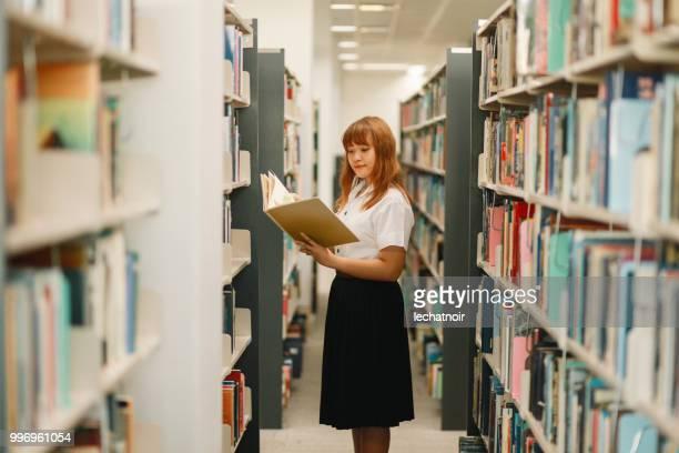 Junge asiatische Studentin Lesung in der Campusbibliothek