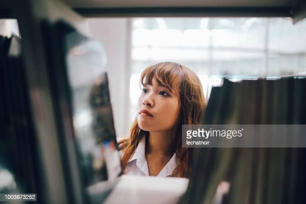 young asian student searching for books in the campus library - library stock pictures, royalty-free photos & images