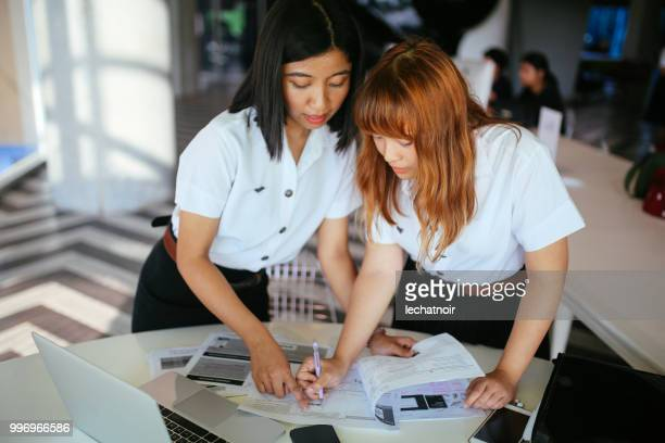 young asian students in uniforms studying together in bangkok, thailand - very young thai girls stock photos and pictures