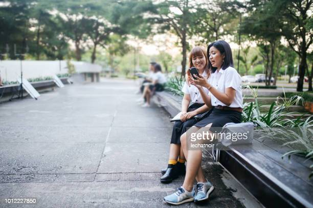 young asian students in uniforms taking a selfie in front of the university - very young thai girls stock photos and pictures