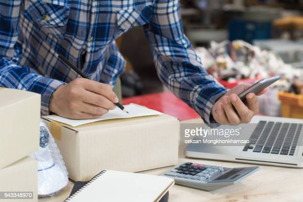 Young asian teenager owner business woman work at home for online shopping,writing the order and preparing package product with office equipment, entrepreneur and alpha generation life style concept