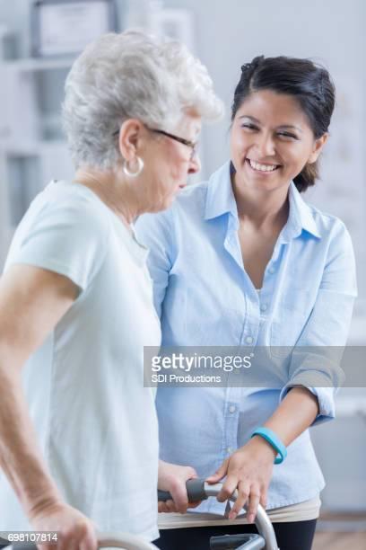 Junge asiatische Therapeut hilft älteren Patienten mit walker