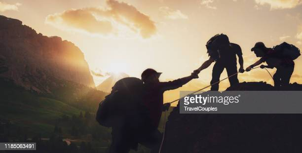 young asian three hikers climbing up on the peak of mountain near mountain. people helping each other hike up a mountain at sunrise. giving a helping hand. climbing. helps and team work concept - image stock pictures, royalty-free photos & images