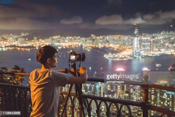 young asian tourist adventure take photo of the hongkong cityscape skyline at victoria peak the famaus tourist place in hong kong - tripod stock pictures, royalty-free photos & images