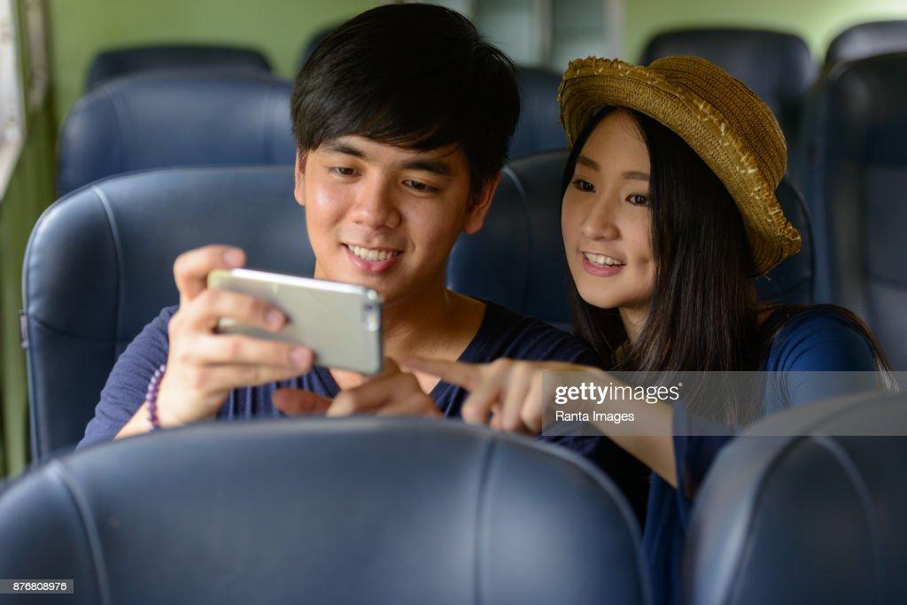Young Asian tourist couple together at Hua Lamphong railway station in Bangkok Thailand : Stock Photo