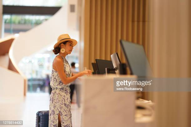 young asian tourist woman with suitcase standing in front of hotel reception counter waiting for check in - guest stock pictures, royalty-free photos & images