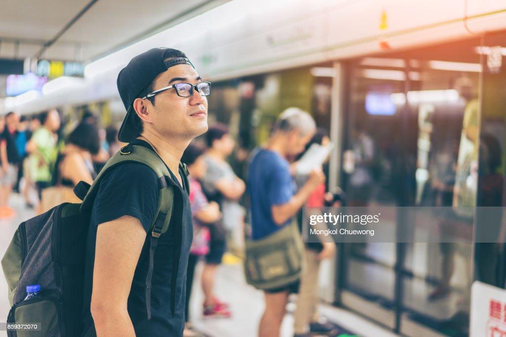 Young asian traveler waiting for transportation underground at Hong Kong MTR : Stock Photo