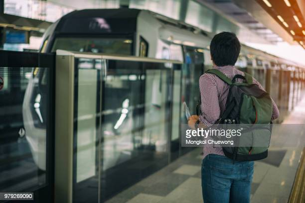 Young asian traveler waiting Mass Rapid Transit (MRT) train in Kuala Lumpur. MRT system forming the major component of the railway system in Kuala Lumpur, Malaysia.