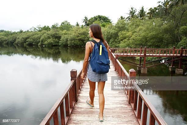 Young Asian traveler walking on a bridge