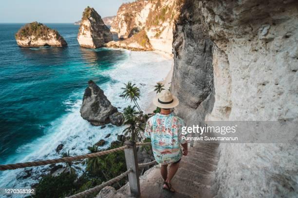 young asian traveller walking down to diamond beach in a morning sunrise in summer season. nusa penida island near bali island, indonesia - nusa penida stock pictures, royalty-free photos & images