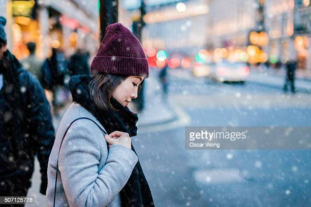 Young Asian walking on the street under snow