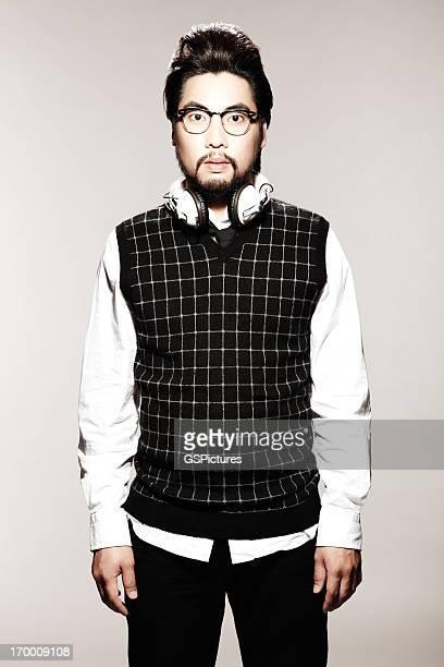 若いアジア着用セーターと白のヘッドフォン