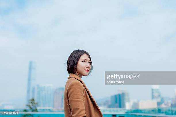 Young Asian woman against city background